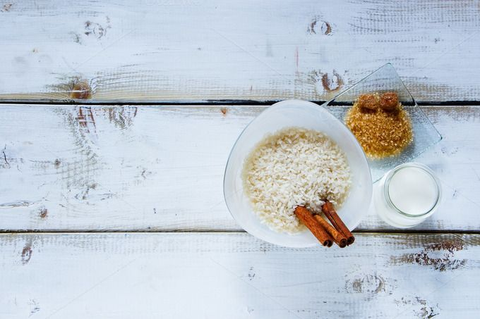 #Ingredients for making rice pudding  Top view of old table with ingredients for making rice pudding. Bowl of white uncooked rice brown sugar cinnamon sticks and jug of milk or cream over wooden background space for text