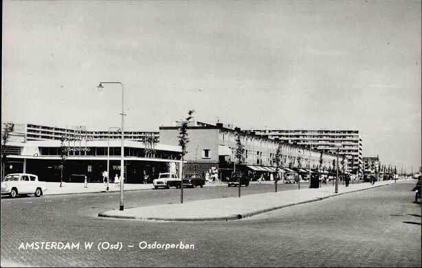 1958 ca Gezicht door de Osdorperban in oostelijke richting. De eerste zijstraat naar links is de Nieuwe Laan. Winkels aan de even zijde van de straat. Een inmiddels afgebroken vestiging van kruidenier De Gruyter.
