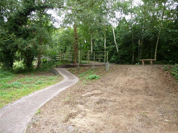 Hunt Nature Park, Shalford. Northern junction  of the woodland path with the Downs Link. The railings in the background are on the Downs Link where it rests on the original railway bridge over Cranleigh Waters. September 2013.