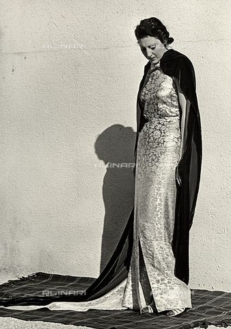 """Model in evening dress created by the Italian couture house """"Dragoni"""". The article is complemented by a long velvet mantle1935 - 1939 (C) Bogino, LuisFratelli Alinari Museum Collections, Florence"""