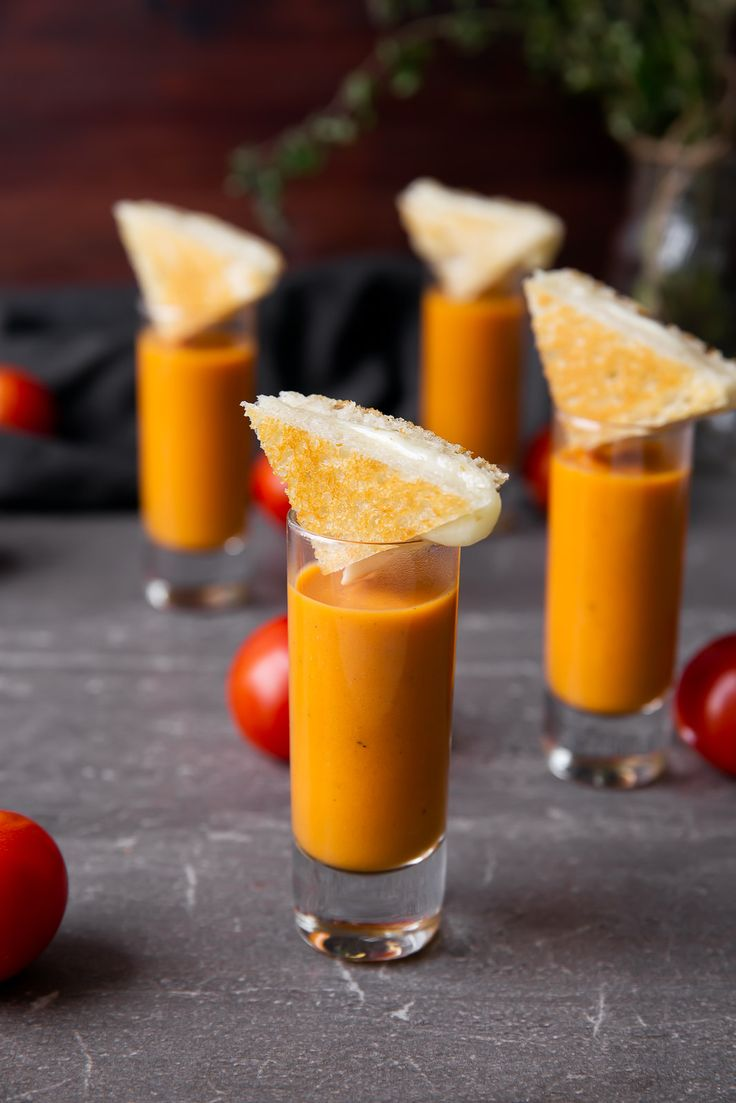 Outrageous Tomato Bisque Shooters topped with grilled cheese triangles! Perfect for a crowd.