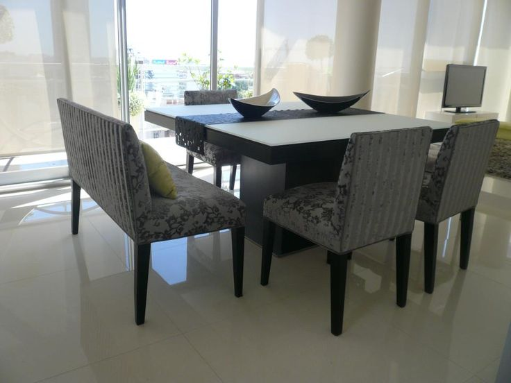 Las mesas cuadradas son muy elegidas a la hora de ambientar un comedor. Para darle un toque distinto, en vez de optar por ocho sillas iguales, podemos incorporar bancos para dos personas, tapizados en la misma tela.