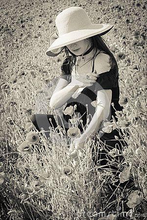 Portrait of summer gothic woman sitting on poppies field in Castelluccio di Norcia, Parco Nazionale dei Monti Sibillini - Umbria - Italy.