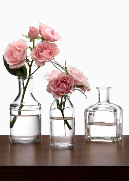 Clear glass bottle bud vases create quick and easy for Glass bottle centerpiece ideas