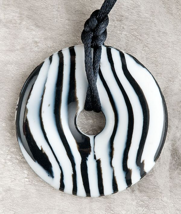 Silicone teething pendant safe for baby to chew and rub on sore gums during teething. This is the Zebra!