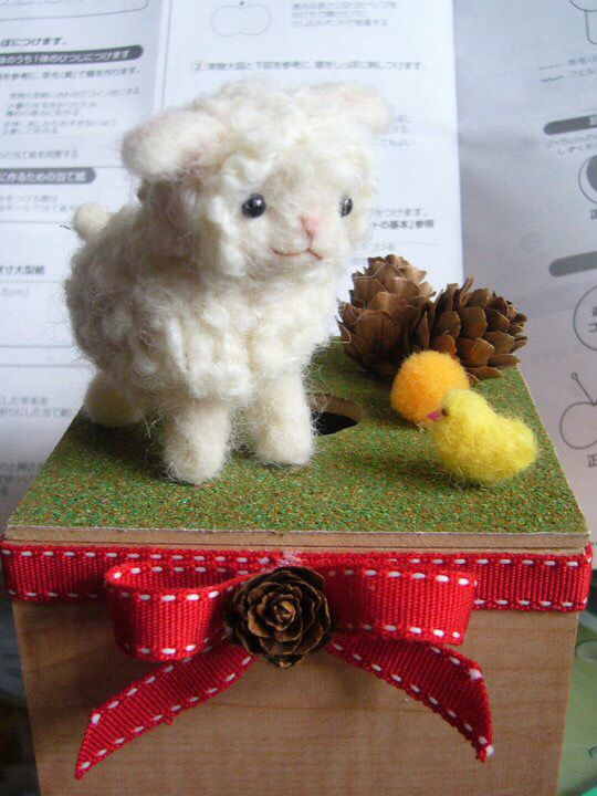 Sheep with little bird made of wool
