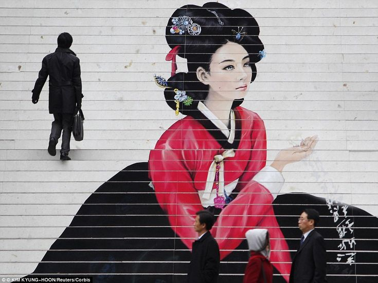 Costumed woman painted to at the front of a Seoul art centre on the stairs to promote a local opera