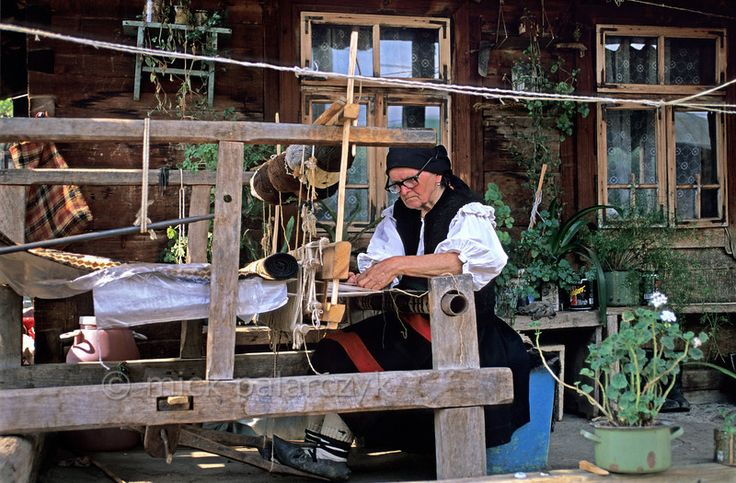 [ROMANIA.MARAMURES 23.658] Working on an old loom in front of her house this inhabitant of Botiza village uses wool that has been coloured by plant extracts. Photo Mick Palarczyk.