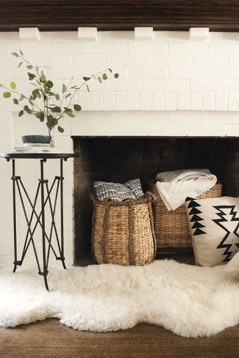 Warm up a nonworking fireplace with cozy accessories such as pillow-and-throw-filled woven baskets, a plush sheepskin rug and a little branch of eucalyptus in a vase, . An added benefit: Easy access to warm blankets on cold evenings.