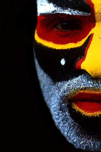 Aboriginal man with aboriginal colours of yellow, red & black in his face paint.