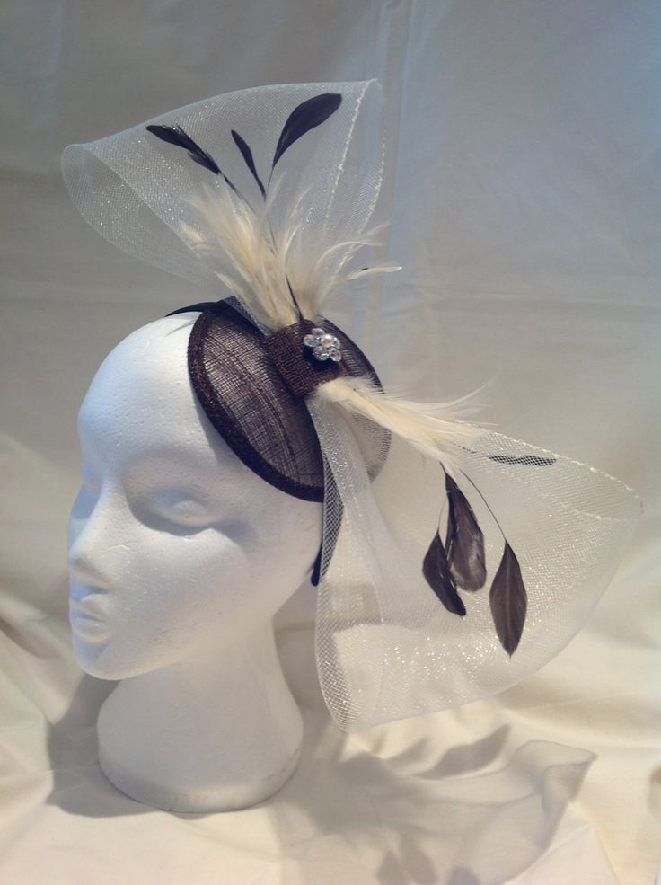 A fascinator by fascinators by Julie the Helena is a large fascinator on a chocolate brown sinamay base and black head band with a large crinoline buttermilk bow centre piece and matching chocolate brown and buttermilk feathers. A diamante jewel is the centre piece of the bow with a pearl detail. $100 AUD. Found in the Chocolatte collection on the website.