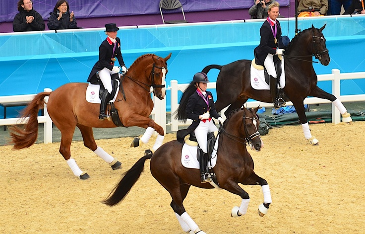 History-making victory gallop: Team GB dressage gold medalists Laura Bechtolsheimer on Mistral Hojris, Charlotte Dujardin on Valegro, and Carl Hester on Uthopia.
