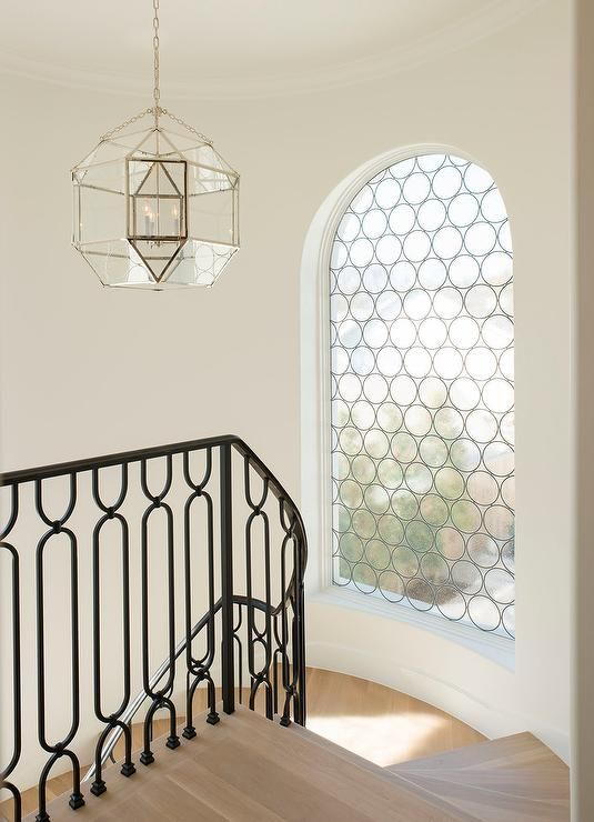 Winding staircase is fitted with an iron handrail and iron balusters and gray wash wood stair treads illuminated by an arched window as well as a Suzanne Kasler Morris Lantern.