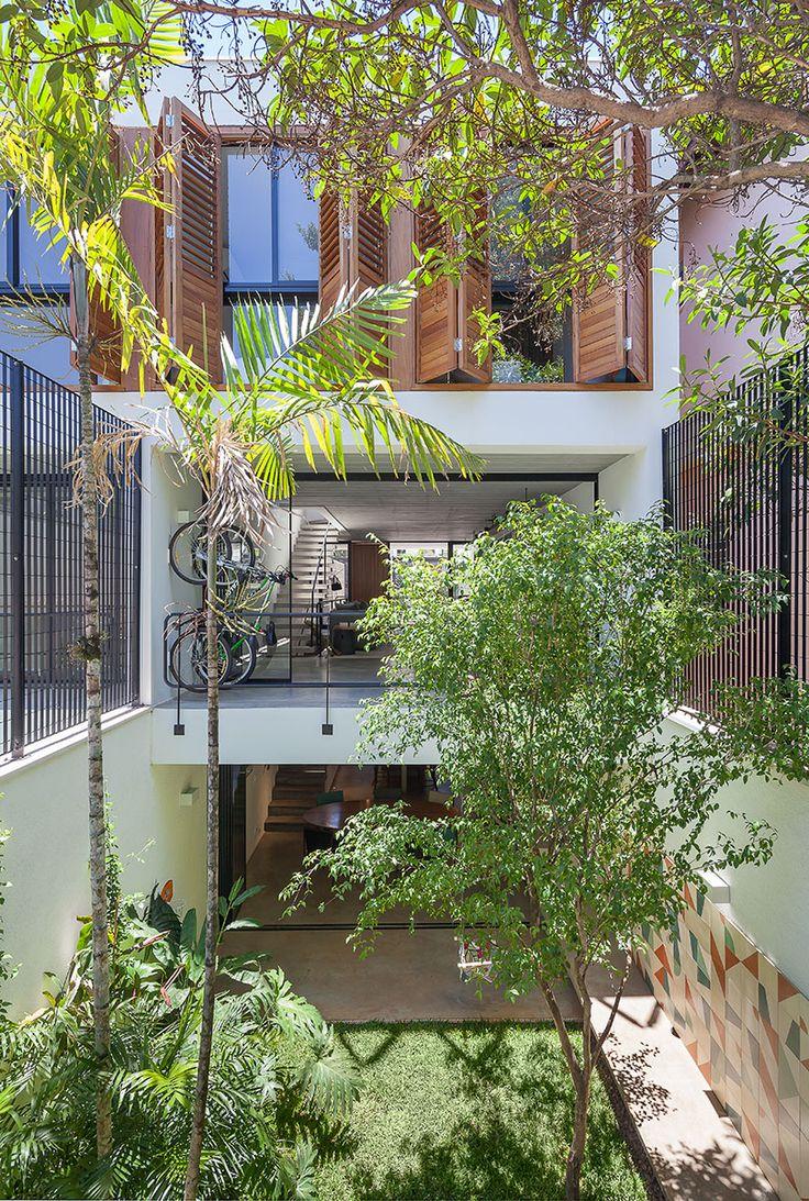 Decoração de casa geminada com luz natural. Fachada com plantas e vidro.