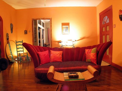 The deep red couch and door along with the orange create a for Red and yellow living room ideas