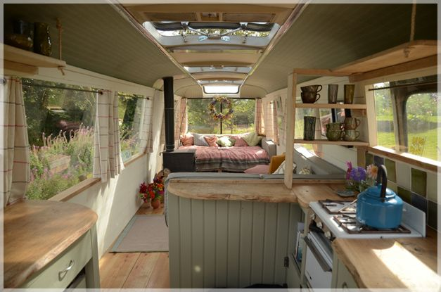 "Converted Camper becomes Majestic Bus - ""The bus has a beautiful wooden floor, painted pine boarding and a well thought-out dining/kitchen area with hand-built units, oak worktops, a gas cooker and a fridge. At the back is a cosy double bed and a wood-burning stove placed on an old flagstone."""