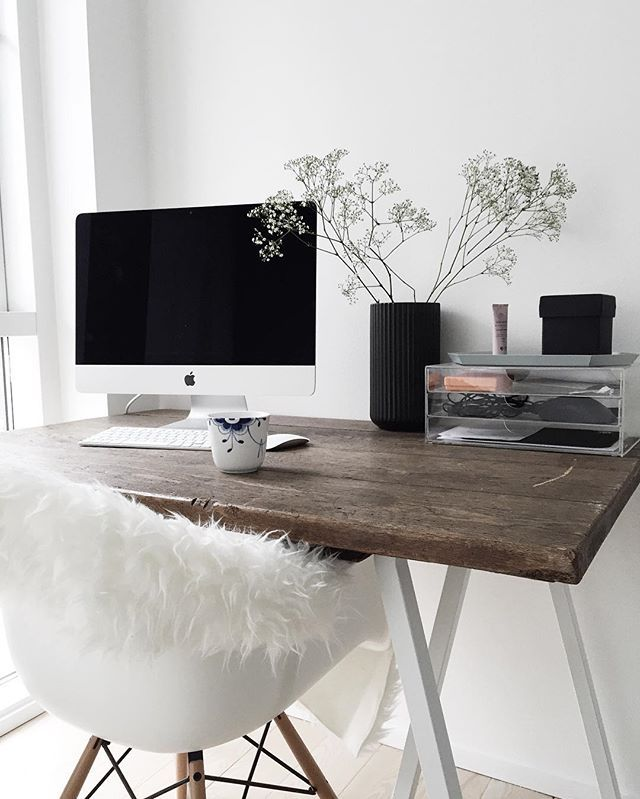 Cozy Scandinavian home office with a rustic feel thanks to the old wood surface of the desk and the fuzzy faux sheepskin.