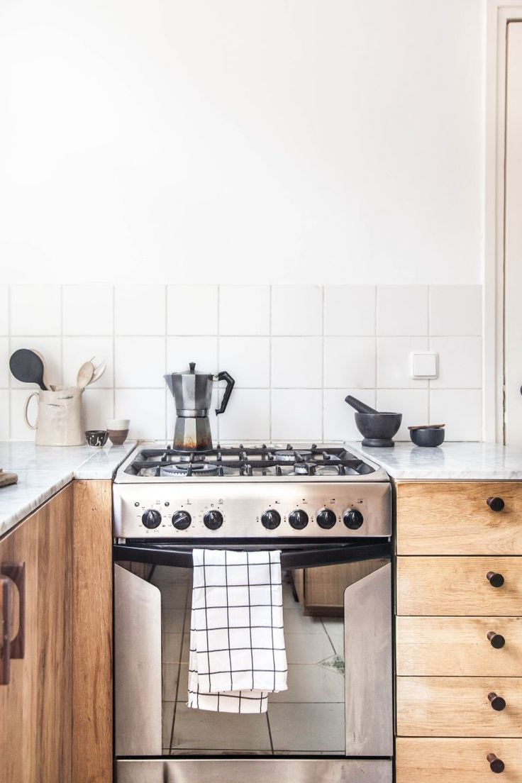 Subway tile, light washed wood vintage cabinets, stainless steel stove, French press