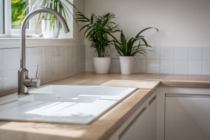 Sustainable Kitchens - Minimalist White Kitchen with Warm Accents. Gorgeous flat panel kitchen with j handles painted in Farrow & Ball All White. The oak worktop works well with the Ikea Hällviken sink and Ikea Ringskär tap to make the area feel warm. The white square tiles add a contemporary look.