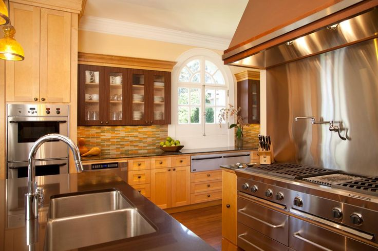 This spacious, contemporary kitchen features commercial appliances for serious cooking. A white arched window and colorful subway backsplash add a feminine look.