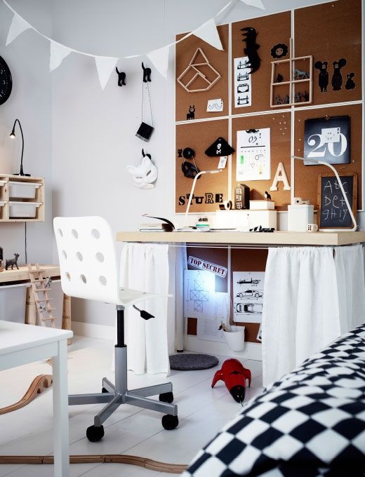 Eine Kinderzimmerwand mit 6 VÄGGIS Pinnwänden in Weiß mit einem Schreibtisch aus Kiefernholz darunter, an dem weiße Gardinen befestigt wurden.