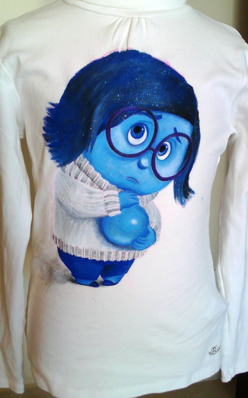 """Hand painted girl's t shirt, featuring Sadness, from the movie """"Inside Out"""". The colors are non-toxic, water based, permanent fabric colors."""