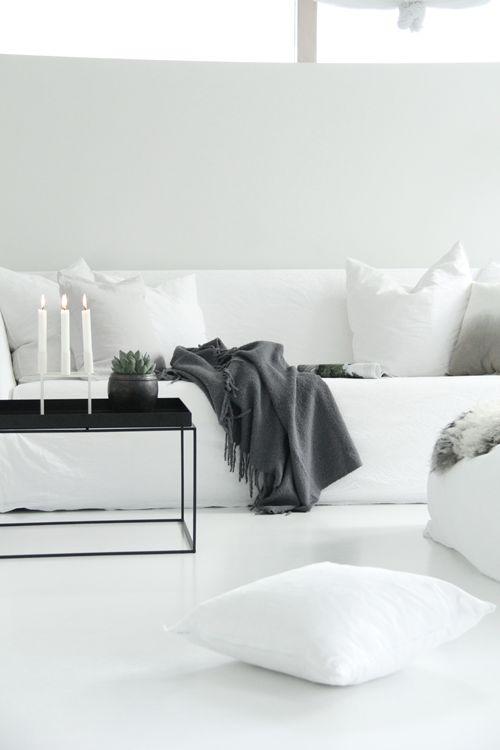 contemporary pure white living room and sofa - fabulous styling using grey cushions and throw with black metal coffee table - the home of elisabeth heier: stue