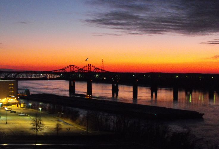 A beautiful evening picture of a towboat with a huge load going north while a smaller boat making it way south at the bridges on the MS River.  (Vicksburg, MS)