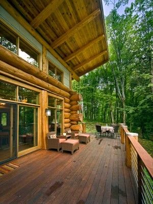 """The Davis family and their guests spend most of the summer months out on the 40-foot wrap-around deck that overlooks the property sloping down to the lake. Constructed of Ipe with stainless steel guard rails, the deck sits 10 feet off the ground. """"You feel like you're floating out in the trees,"""" says Scott. The 8-foot roof overhang means they can enjoy being outside even during a rain shower."""