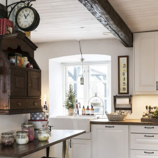 На кухне современная мебель соседствует с антикварной, а окно украшает елочка в горшочке.