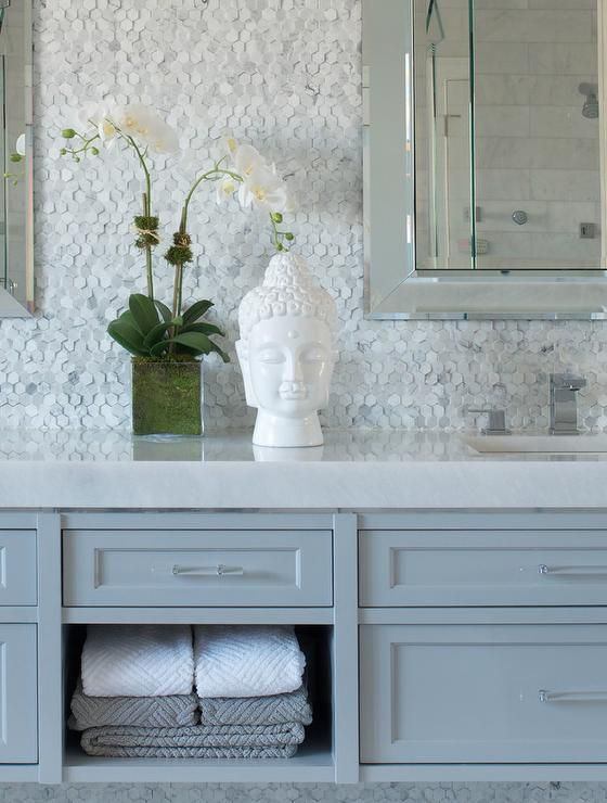 Zen bathroom features a gray double washstand accented with glass pulls paired with white countertops and a marble hex tiled backsplash adorned with beveled vanity mirrors alongside a white Buddha head and orchid.
