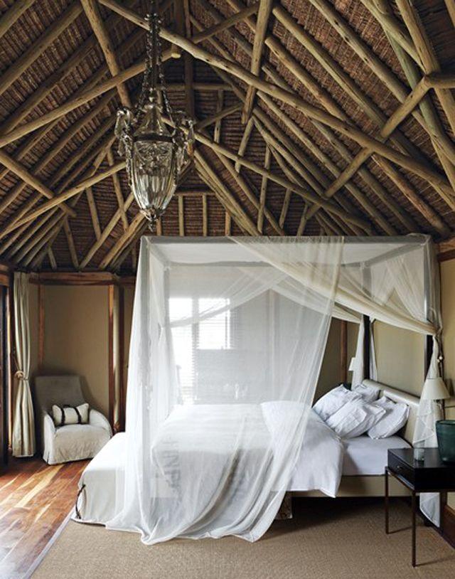 Plafond haut en poutres apparente et lit baldaquin de voile blanc