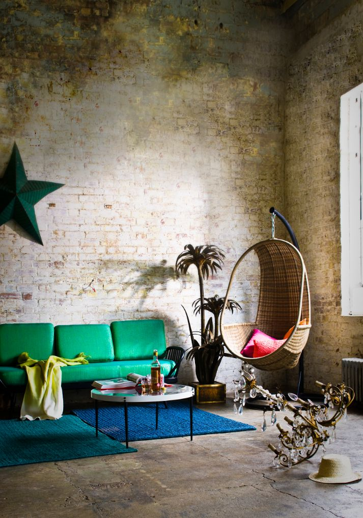 A swinging wicker chair and Kelly green sofa comfy up an industrial living room.  Swoon de chambre: séjour Chambre tropicale | Life.Style.etc