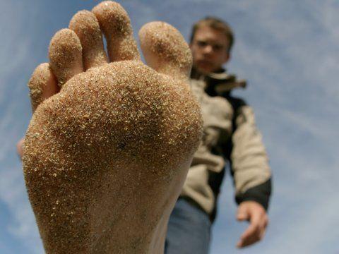 Close up van voet met zand. Hoe groot is jouw voetafdruk?
