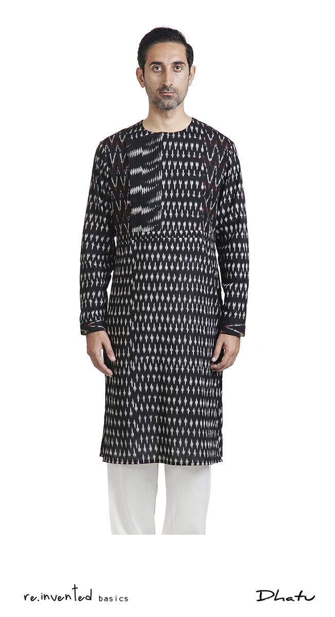 Single Ikat Occasion Wear Achkan Kurta by Dhātu. Heritage and Ideals, Codes and Standards. A knee length dress tunic reminiscent of pre Raj India featuring a side opening with a loop (baghal bandh) and pleat details on bib. Cleverly constructed with concealed closures and facings to avoid visible stitch lines. 'Elbow pleat' re-structures the mandatory ease away from the cuff for an ergonomic slim sleeve.