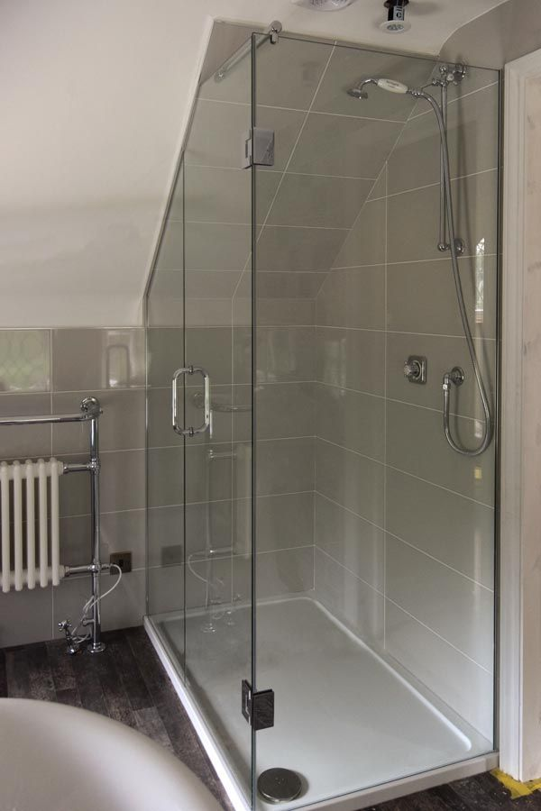 Bespoke shower cubicle for loft conversion installed by Creative Glass Studio in Crawley. Mini shower door seals, polished chrome hinges and a pull handle.