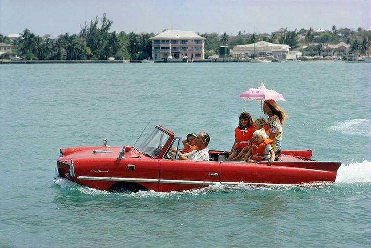 """Slim Aarons, Sea Drive, 1967: Film producer Kevin McClory and wife Bobo Segrist and family in an """"Amphicar"""" at the harbour at Nassau."""