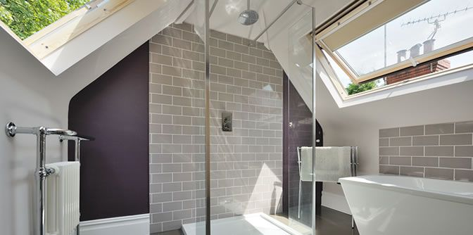 This loft bathroom has the light spacious feel we'd love. God knows how much the long thin Velux are but they'd work so nicely on a sloped roof!