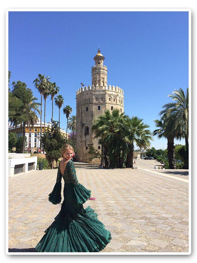 María León junto a la Torre del oro vestida de flamenca