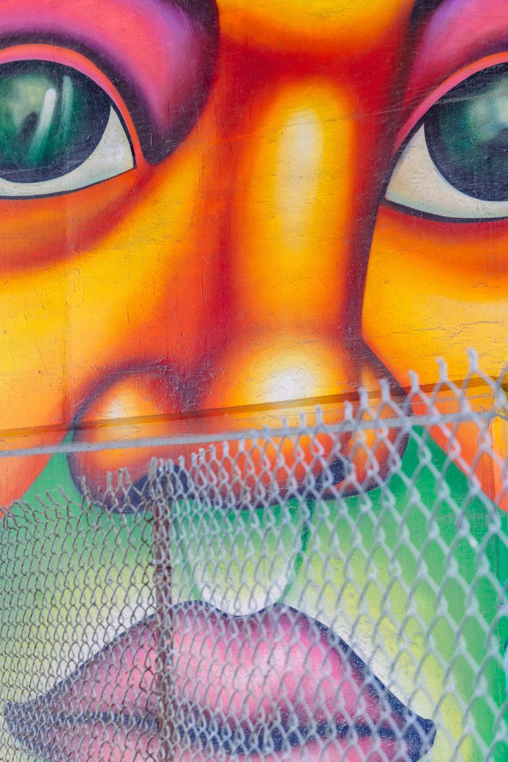 Colorful urban street art graffiti mural of human face behind chain link fence