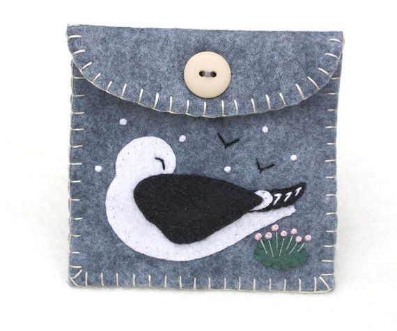 A coin purse handmade in grey felt, with a sleeping Black backed gull nested among the sea pink flowers. With cream felt lining, blanket stitched edges and a button fastening. For coins, jewellery or other treasures, perfect for a seaside holiday. Size (excluding stitched seams) 9cm