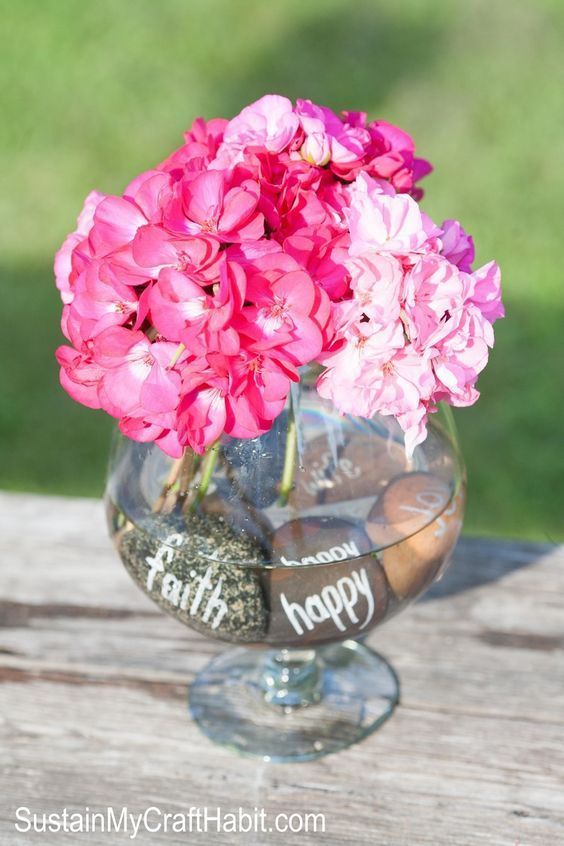 DIY Inscribed beach stone centerpiece. When you're at the beach next collect a dozen or so medium sized rounded stones. Write wedding friendly words on each stone and place them inside s clear vase with fresh flowers. A lovely idea for a wedding, shower or other special event. Click through for the full tutorial.