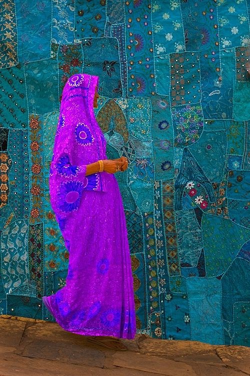 woman walking past a tapestry, jodphur, rajasthan, india