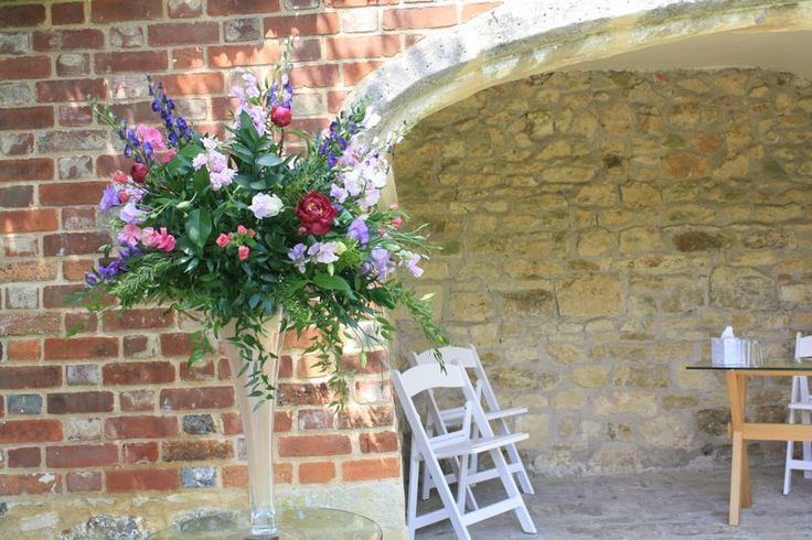 A tall flute vase at  the top of the aisle in the garden at Notley Abbey