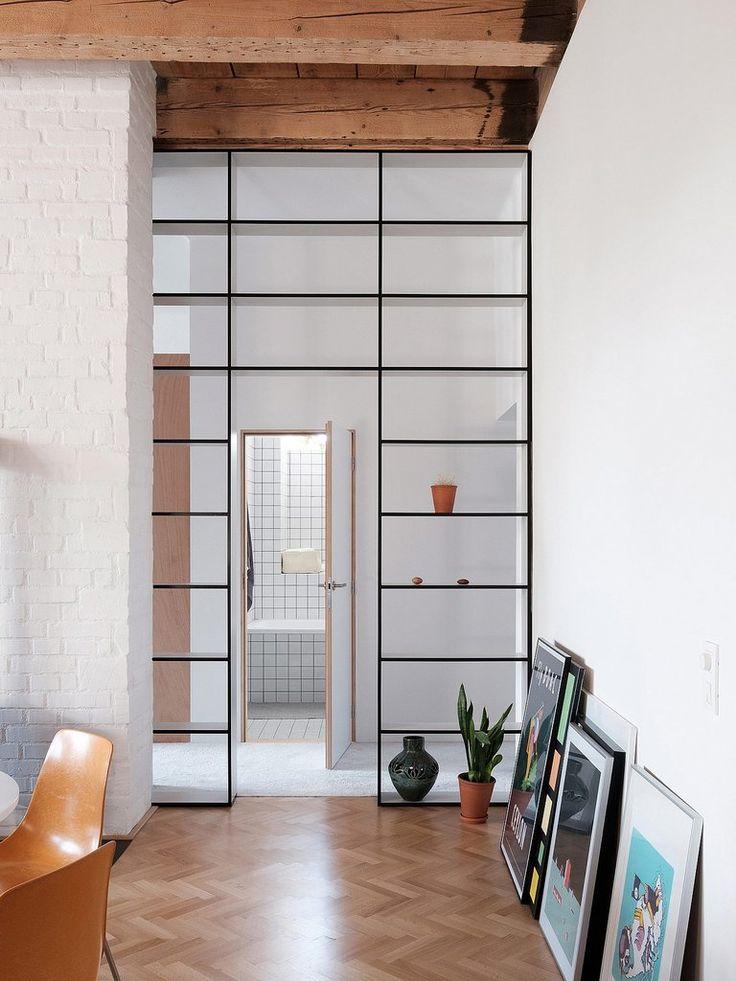 Широкий дверной проем использован с пользой - в нем установлены сквозные стеллажи.  (квартиры,апартаменты,интерьер,дизайн интерьера,мебель,минимализм,гостиная,дизайн гостиной,интерьер гостиной,мебель для гостиной) .