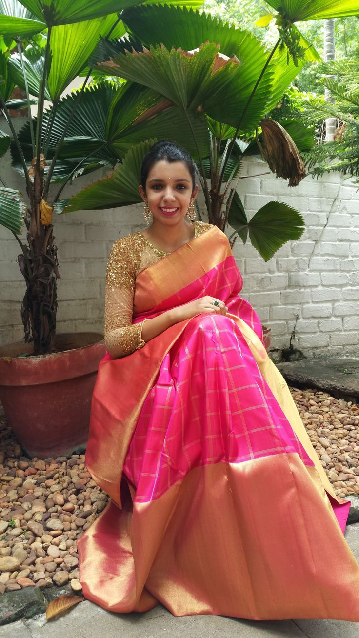 Neon pink kanchipuram silk with a retro style checks and pure zari border and pallu. I love the blouse and chaandbalis which make it look so perfect..