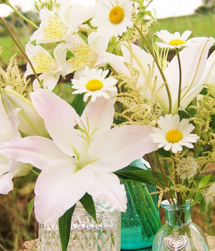 An eclectic mix of containers for table clusters is just perfect for a boho or a garden wedding. Here we have white lilies, daisies, astrantia, astilbe and alstroemeria. Florissimo, Shropshire