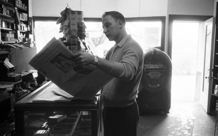 Dodger southpaw and 1955 World Series MVP Johnny Podres reads about his own and his teammates' exploits while visiting a store in his hometown of Witherbee, New York — a small mining town in the Adirondacks, a few hundred miles north of Brooklyn.
