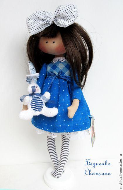 Купить или заказать Малышка с зайкой в интернет-магазине на Ярмарке Мастеров. Небольшая куколка с зайкой в руке. Волосы можно бережно расчесывать. Под платьицем нижняя юбка, украшенная кружевом. Зайка сшит из махровой ткани, крепится к ручке при помощи резинки. Кукла стоит с опорой. Подставка от меня в подарок. ________________________________________ Кукла приедет к Вам в подарочном капроновом пакетике с красивой бирочкой.
