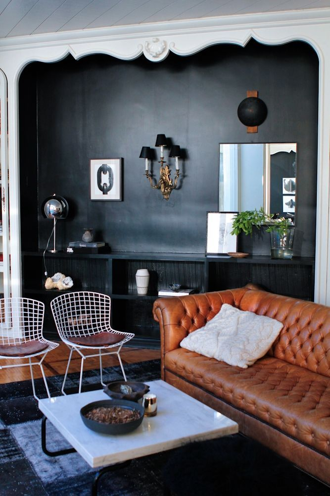 a dark alcove with 3 chic light sources, Bertoia chairs & a cognac leather Chesterfield sofa